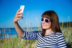 Mujer hermosa que usa el teléfono elegante en la playa Fotografía de archivo