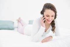 Mujer hermosa que usa el teléfono móvil en cama Fotografía de archivo libre de regalías