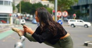 Mujer hermosa que usa el teléfono móvil mientras que la pierna estiró en las verjas en la ciudad 4k almacen de video