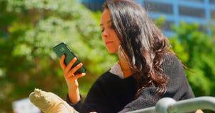 Mujer hermosa que usa el teléfono móvil mientras que la pierna estiró en las verjas en la ciudad 4k metrajes