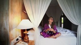 Mujer hermosa que usa el tel?fono en la cama que maneja el hogar conectado elegante con el app m?vil almacen de video