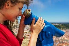 Mujer hermosa que usa los prismáticos pagados moneda en la alta colina y la mirada Imágenes de archivo libres de regalías