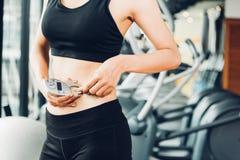 Mujer hermosa que usa medida gorda del calibrador después de entrenamiento del ejercicio foto de archivo