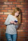 Mujer hermosa que usa smartphone de alta tecnología contra la pared de ladrillo. foto de archivo