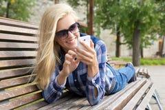 Mujer hermosa que usa smartphone en banco en parque Fotografía de archivo