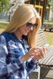 Mujer hermosa que usa smartphone en parque Fotos de archivo libres de regalías