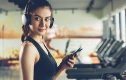 Mujer hermosa que usa smartphone móvil durante entrenamiento fotografía de archivo