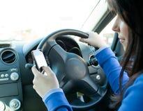 Mujer hermosa que usa su teléfono celular mientras que conduce Imagen de archivo