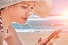 Mujer hermosa que usa sus datos del teléfono móvil mientras que se relaja en la playa imágenes de archivo libres de regalías