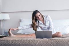 Mujer hermosa que usa un cuaderno en cama y estirar Foto de archivo