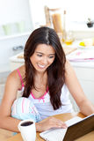 Mujer hermosa que usa una computadora portátil en la cocina Imagen de archivo libre de regalías
