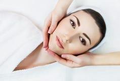 Mujer hermosa relajante joven que tiene masaje facial Foto de archivo