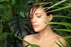 Mujer hermosa rodeada por las plantas verdes Concepto del balneario y tratamiento natural del skincare imagenes de archivo