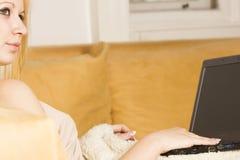 Mujer hermosa rubia con la computadora portátil en la cama Imagen de archivo