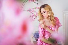 Mujer hermosa rubia en bata rosada imagen de archivo libre de regalías
