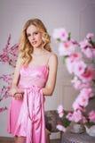 Mujer hermosa rubia en bata rosada fotografía de archivo libre de regalías
