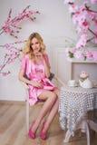 Mujer hermosa rubia en bata rosada imágenes de archivo libres de regalías