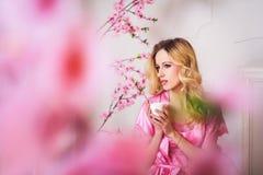 Mujer hermosa rubia en bata rosada foto de archivo libre de regalías