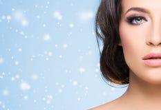 Mujer hermosa sobre fondo del invierno con las escamas de la nieve Concepto de la Navidad foto de archivo libre de regalías