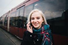 Mujer hermosa sonriente de los jóvenes que habla en el teléfono en el fondo del tren moderno Fotos de archivo