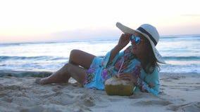 Mujer hermosa sonriente del turista joven en gafas de sol y el sombrero que miente en la playa arenosa y bebidas del paraíso trop almacen de metraje de vídeo