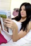 Mujer hermosa sonriente en revista de la lectura de la cama Fotografía de archivo libre de regalías