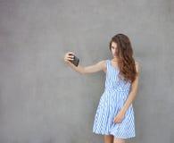 Mujer hermosa sonriente feliz joven en vestido ligero con el pelo rizado moreno largo que presenta contra la pared en un caliente Foto de archivo