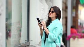 Mujer hermosa sonriente que admira tomando la foto del escaparate de cristal de la tienda usando smartphone metrajes