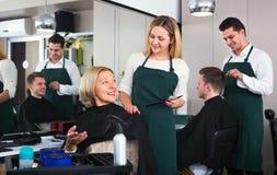 Mujer hermosa sonriente que corta el pelo femenino del pensionista Imagen de archivo libre de regalías