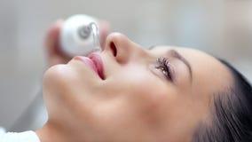 Mujer hermosa sonriente que goza de la cara ultrasónica que limpia en el primer del salón de belleza almacen de metraje de vídeo