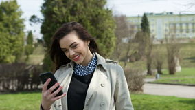 Mujer hermosa sonriente que manda un SMS con su teléfono almacen de video