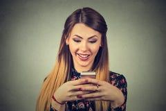 Mujer hermosa sonriente que manda un SMS en su teléfono móvil Imagen de archivo