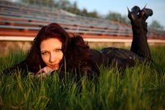 Mujer hermosa sonriente que pone en hierba Imagenes de archivo