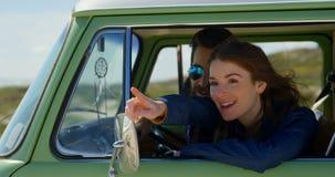 Mujer hermosa sonriente que señala el finger que muestra algo servir en el coche 4k metrajes