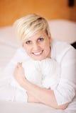 Mujer hermosa sonriente que se relaja en cama foto de archivo