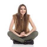 Mujer hermosa sonriente que se sienta con las piernas cruzadas Imagen de archivo libre de regalías