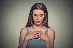 Mujer hermosa, tímido, jugando nervioso con las manos que miran abajo fotografía de archivo