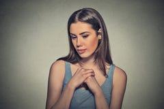 Mujer hermosa, tímido, jugando nervioso con las manos que miran abajo imagenes de archivo