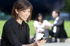 Mujer hermosa Texting y café de consumición Fotografía de archivo libre de regalías