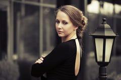 Mujer hermosa triste de la moda en vestido negro en la calle de la ciudad Foto de archivo