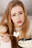 Mujer hermosa triste, preocupante que come el helado. Imagenes de archivo