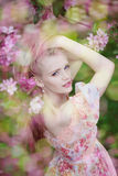 Mujer hermosa y árbol floreciente Chica joven de la belleza en jardín Imágenes de archivo libres de regalías