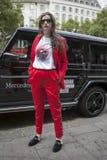 Mujer hermosa y elegante en el traje rojo que presenta durante la semana de la moda de Londres Eudon Choi exterior Imagen de archivo