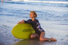 Mujer hermosa y feliz atractiva joven de la persona que practica surf que se sienta en la arena de la playa que lleva a cabo el h fotos de archivo libres de regalías