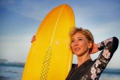 Mujer hermosa y feliz atractiva joven que lleva a cabo vacaciones de verano de goce alegres sonrientes del tablero amarillo en ll imágenes de archivo libres de regalías
