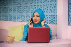 Mujer hermosa y feliz joven en la bufanda musulmán de la cabeza del hijab que trabaja con el funcionamiento del establecimiento d imagenes de archivo