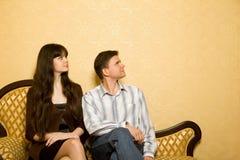 Mujer hermosa y hombre joven que se sientan en el sofá Foto de archivo libre de regalías