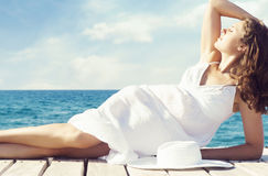 Mujer hermosa y joven que presenta en el vestido blanco en un embarcadero de madera Fotografía de archivo libre de regalías