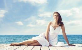 Mujer hermosa y joven que presenta en el vestido blanco en un embarcadero de madera Imagen de archivo libre de regalías