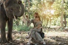 Mujer hermosa y muchacha que juegan con los elefantes Foto de archivo libre de regalías
